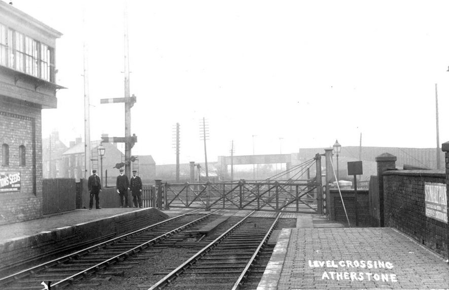 End of railway station platforms at Atherstone.  Level crossing, gates, railway bridge, signals and railway staff. Advertisement for Sutton's seeds on wall of signal box.  1900s |  IMAGE LOCATION: (Warwickshire County Record Office)