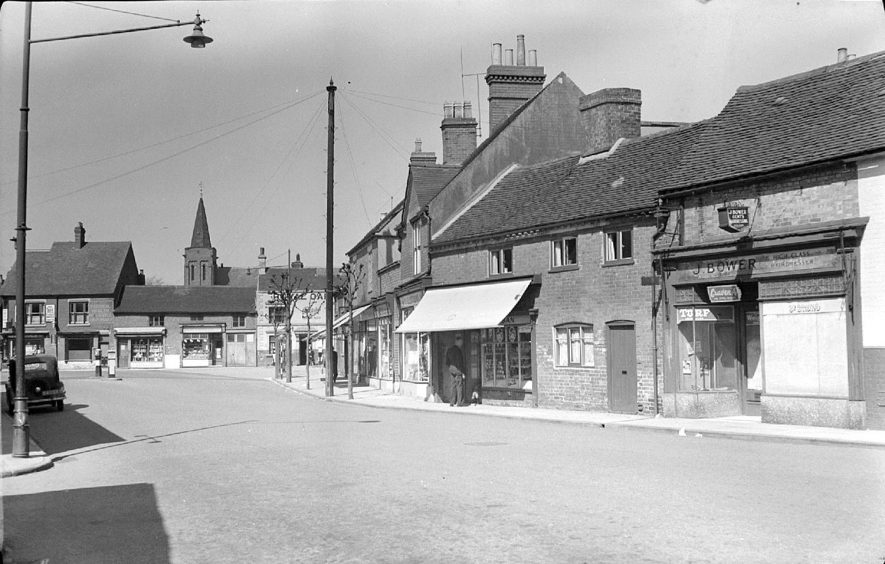 Attleborough Green, Nuneaton.  Showing a street with shops and a church spire beyond.  1951 |  IMAGE LOCATION: (Warwickshire County Record Office)