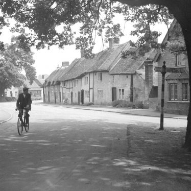 Monks Kirby.  Cyclist making his way through the village