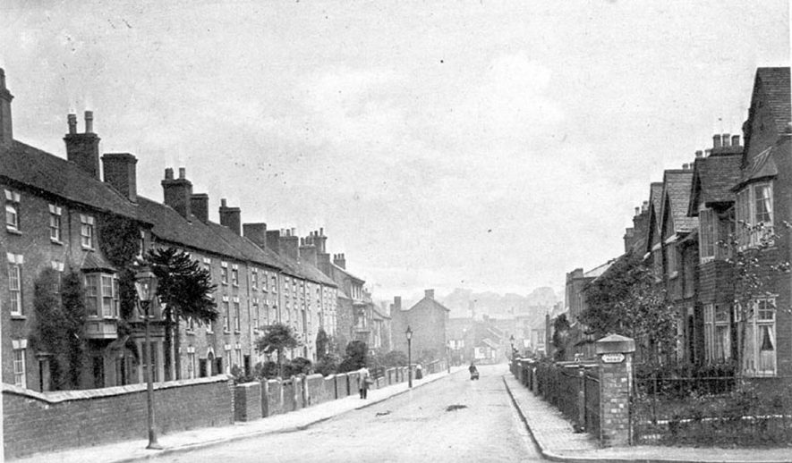 Coleshill Street, Atherstone, with terraced houses and lamp posts. Three figures, one a boy with trolley.  1910s |  IMAGE LOCATION: (Warwickshire County Record Office)