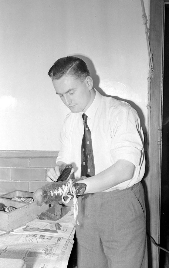 John Deemimg, wing three-quarter for Nuneaton & Warwickshire cleaning his boots at home.  1953 |  IMAGE LOCATION: (Warwickshire County Record Office) PEOPLE IN PHOTO: Deeming, J, Deeming as a surname