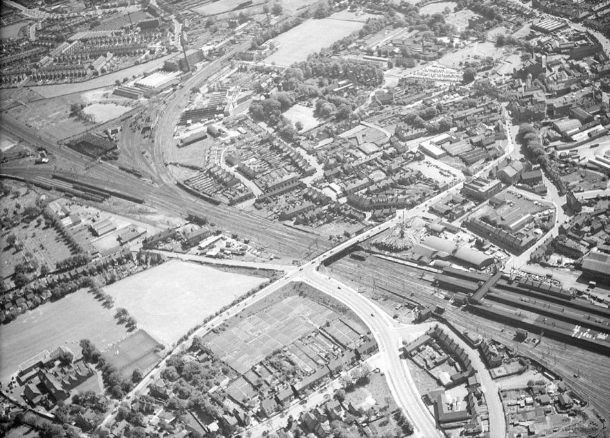 Aerial view of Leicester Road bridge (centre), showing the main railway line (London-Glasgow),  with Trent Valley station on extreme lower right.   Town centre top right.  1957 |  IMAGE LOCATION: (Nuneaton Library)