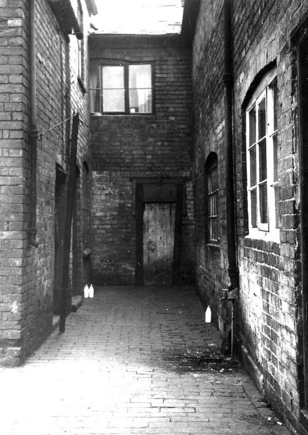 A typical court in Abbey Street, Nuneaton. The ribbon weavers would live and carry on their work in rooms leading on to courts such as this one.  Abbey Street had much housing of this type which must have been squalid and unhygienic.  1920s |  IMAGE LOCATION: (Nuneaton Library)