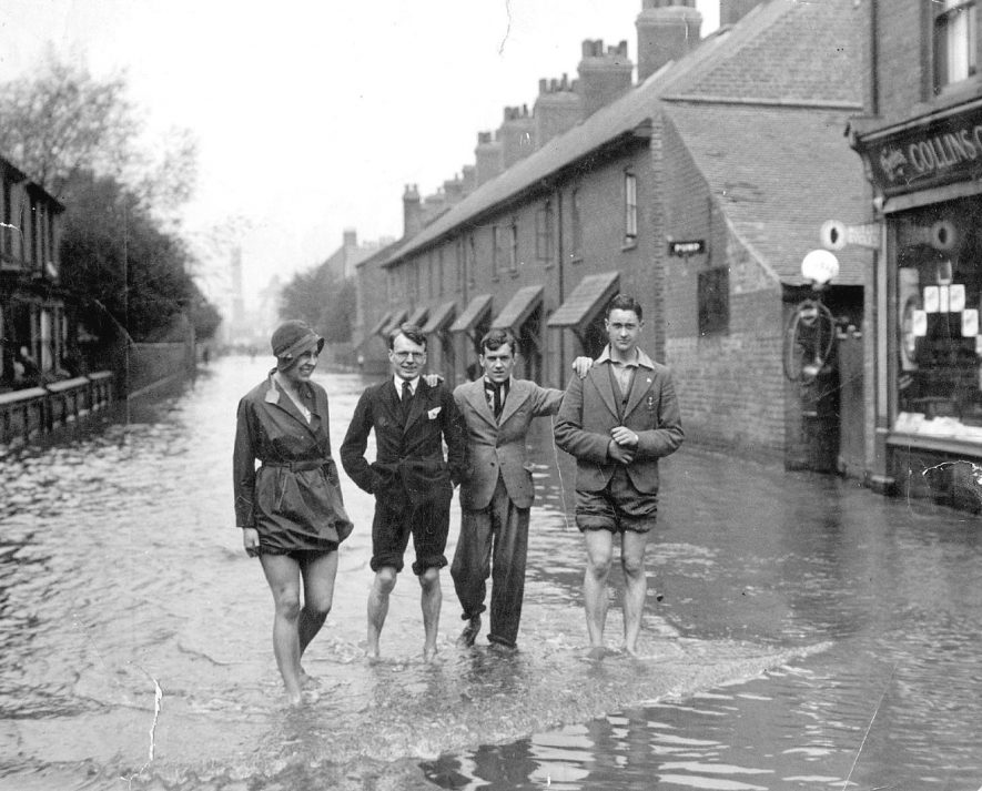 Dugdale Street, looking towards Queens Road, Nuneaton during the floods in 1932.From left to right - Beth Harris, anon, Alan Beamish and Jack Harris.  1932 |  IMAGE LOCATION: (Nuneaton Library) PEOPLE IN PHOTO: Harris, Jack, Harris, Beth, Beamish, Alan