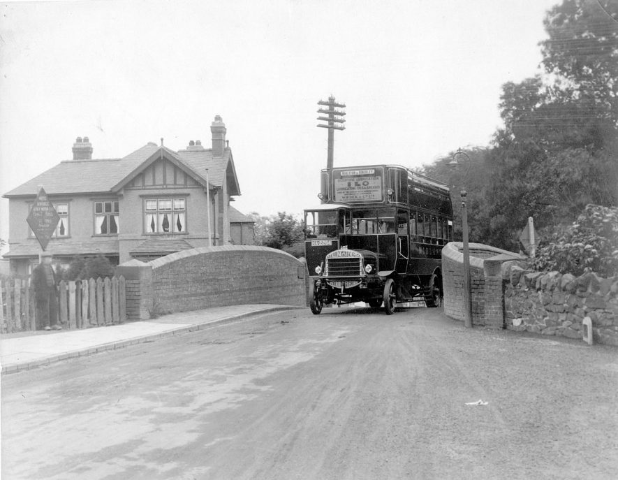 Coventry Road, Nuneaton, before bridge widening.  This was a notorious bottleneck at Wharf Bridge over the Coventry Canal at Coton. The Midland Red bus had solid tyres and the engine was a Tilling Stevens.  1920s |  IMAGE LOCATION: (Nuneaton Library)