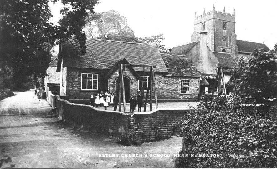 School children in school playground, two women talking in lane and Astley church in the background.  1900s |  IMAGE LOCATION: (Warwickshire County Record Office)