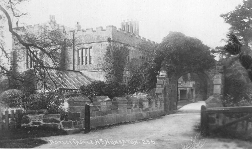 Stone archway entrance to Astley Castle. Part of castle and greenhouse roof.  1900s |  IMAGE LOCATION: (Warwickshire County Record Office)