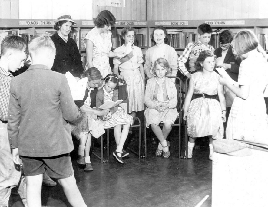 Miss Wilma Cotton organises a play reading in the Children's Library, Nuneaton. Photograph used as a library exhibit during the Charter Celebration Exhibition, July 1957.  1950s |  IMAGE LOCATION: (Nuneaton Library) PEOPLE IN PHOTO: Cotton, Miss Wilma, Cotton as a surname