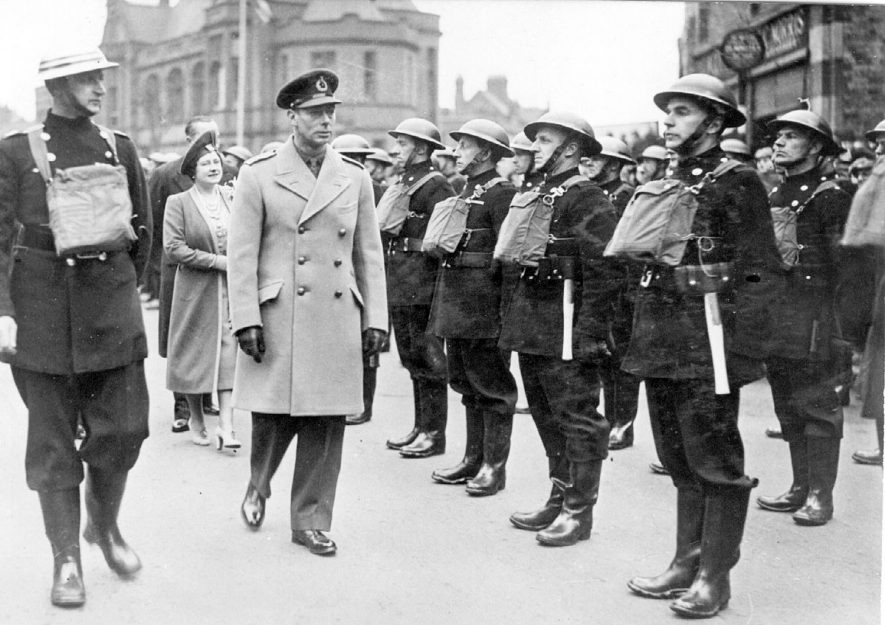 H.M. George VI and Queen Elizabeth reviewing the fire brigade in Coventry Street, Nuneaton. Each man is carrying a gas mask on his chest, an axe in his belt and is wearing standard issue wellington boots. The old police station is in the background.  1940s |  IMAGE LOCATION: (Nuneaton Library) PEOPLE IN PHOTO: Elizabeth II, George VI
