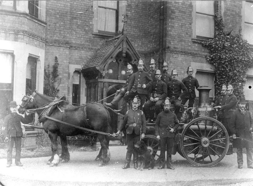Fire engine, being pulled by a team of  two horses, with the firemen and their dog mascot.  1900s |  IMAGE LOCATION: (Nuneaton Library)