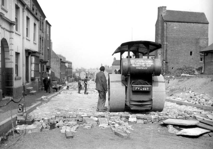Road repairs in Bedworth showing a road roller at work. 1950s[The roadworks were being carried out in Chapel Street(formerly Hob Lane)where it is said there were ghosts because it was marshy at the bottom and the methane from the marsh produced wierd effects.The Hit and Miss pub is on the right of the picture][The Ghost was that of Polly Pinket, murdered(don't know why), who worked at the Hit or Miss. After her demise haunted the Hit & Miss Public House. The Hit & Miss had 33 bedrooms, a Ballroom with stage, a cocktails room, a Snug and the ordinary bar. Larry Grayson (Billy Breen) played the piano in the Bar to entertain the customers at the weekend on a regular basis.] |  IMAGE LOCATION: (Bedworth Library)