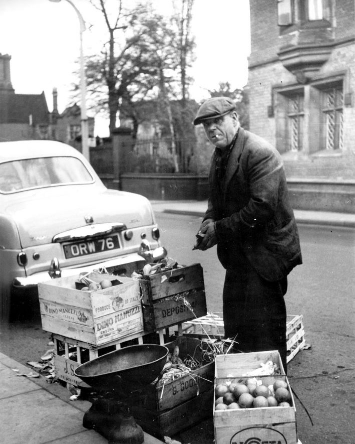 Mr Flanaghan selling apples at the side of the street in Bedworth.  1957 |  IMAGE LOCATION: (Bedworth Library)