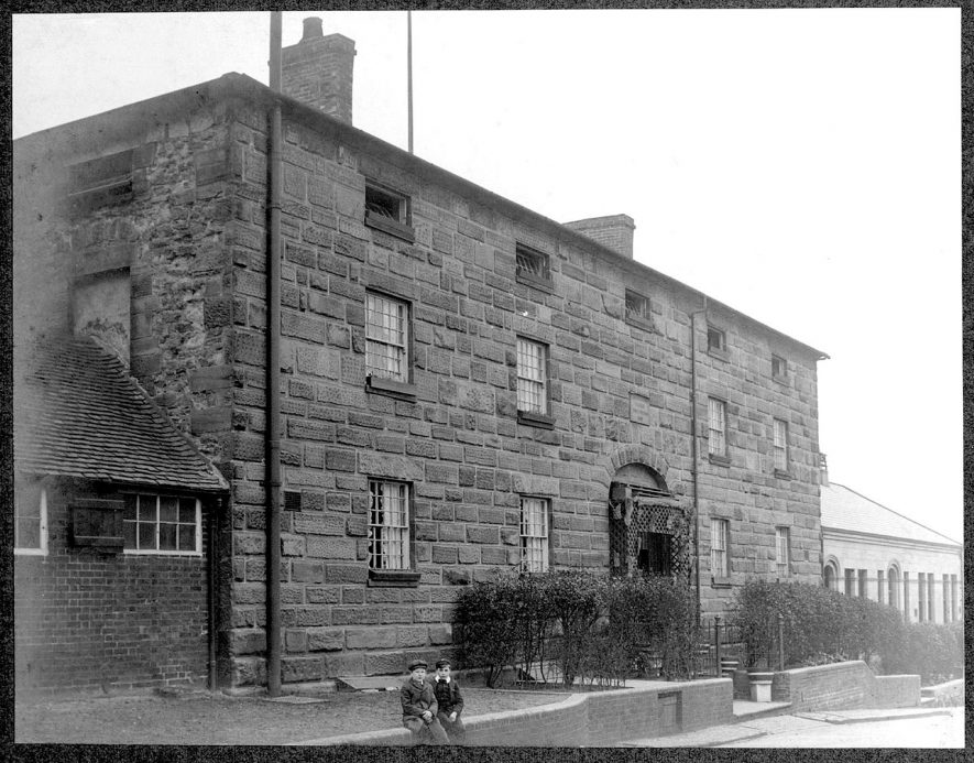 Exterior of The College for the Poor, Chilvers Coton workhouse. Two small boys sitting on wall in front.  1900s |  IMAGE LOCATION: (Nuneaton Library)