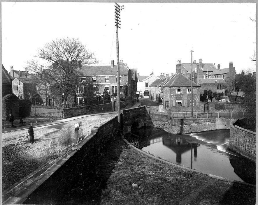 Mill Walk, Nuneaton. River in the foreground, with small bridge over and houses in the background. Part of this is now the site of the Council house.  1900s |  IMAGE LOCATION: (Nuneaton Library)