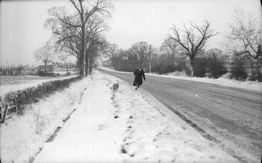 View near Bramcote, looking towards Nuneaton as a woman approaches with her dog.  February 25th 1958 |  IMAGE LOCATION: (Warwickshire County Record Office)