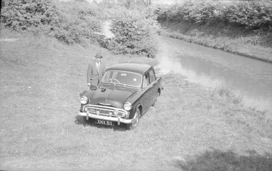 Cyril Bull standing beside his Hillman