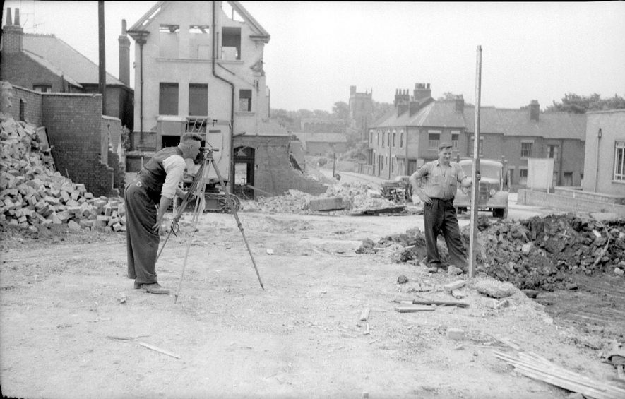 Mr. Percy Grant of 24, Stoney Road, Nuneaton, and foreman on the site uses the Theodolite (left), whilst Mr. Martin Connelly of Birmingham holds the staff. On the left of this view can be seen The Black Horse pub and in the centre background is the tower of Nuneaton Parish Church.  June 13th 1959 |  IMAGE LOCATION: (Warwickshire County Record Office) PEOPLE IN PHOTO: Grant, Percy, Grant as a surnam, Connelly, Martin, Connelly as a surname
