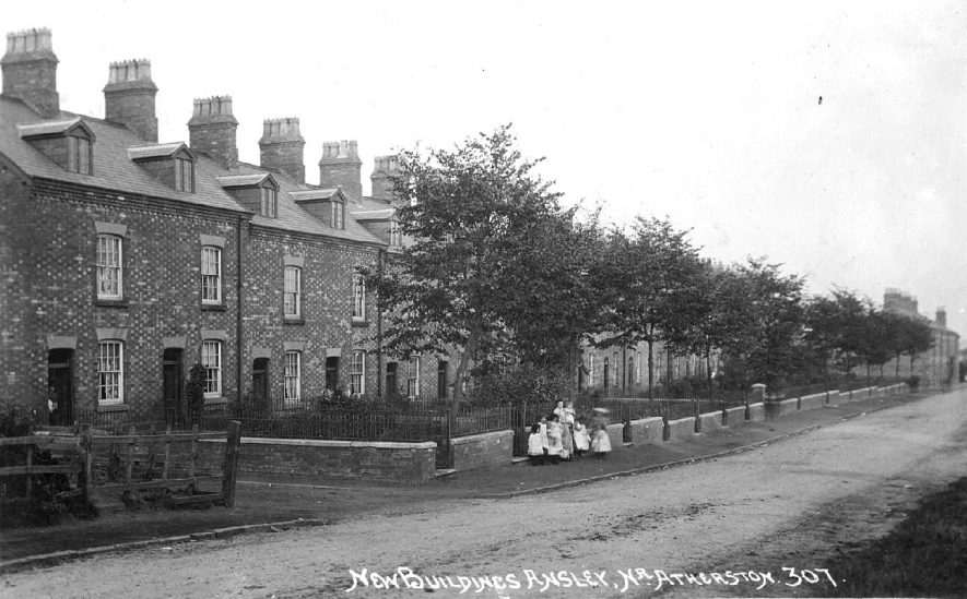 'New Buildings', Beech Terrace, Ansley, showing terraced houses, front gardens and a group of children standing on the pavement.  1910s |  IMAGE LOCATION: (Warwickshire County Record Office)