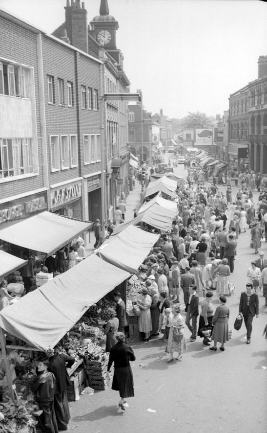 Nuneaton Market Place with stalls and shoppers. View taken from billiard hall situated over Burton's shop.  June 13th 1959 |  IMAGE LOCATION: (Warwickshire County Record Office)