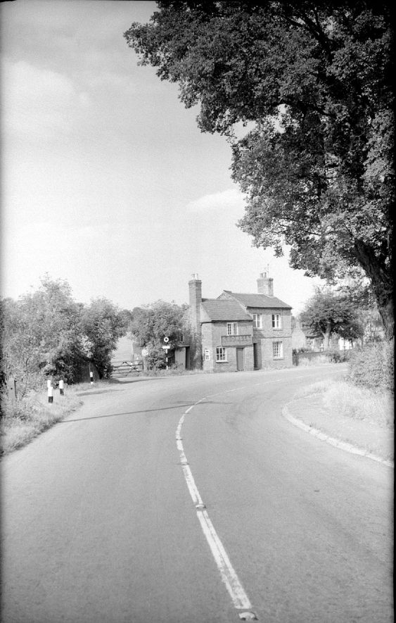 View on the road near Brinklow station and showing, on the left, the gateway to the Fosse Way.  1961 |  IMAGE LOCATION: (Warwickshire County Record Office)