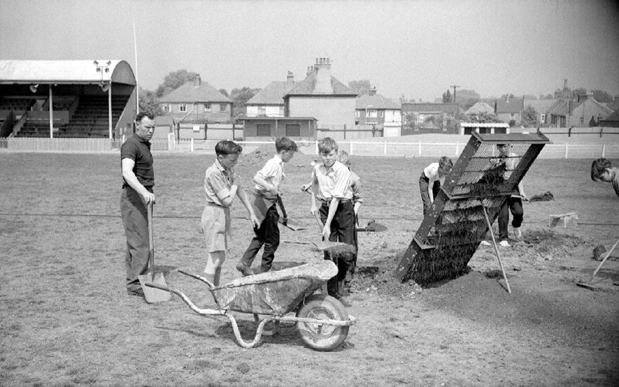 Team Manager, Fred Bodham, with some boys working on the ground at Nuneaton Borough's Football Ground at Manor Park.  1963  [Team Manager should be Fred Badham and not Bodham.] |  IMAGE LOCATION: (Warwickshire County Record Office) PEOPLE IN PHOTO: Bodham, Fred, Bodham as a surname