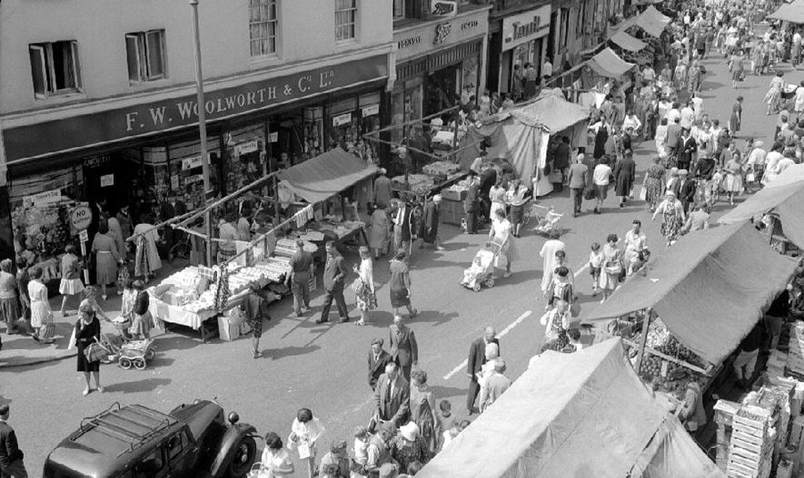 Nuneaton town centre on market day. (Photograph taken from an office window under the Town Clock).  1963 |  IMAGE LOCATION: (Warwickshire County Record Office)