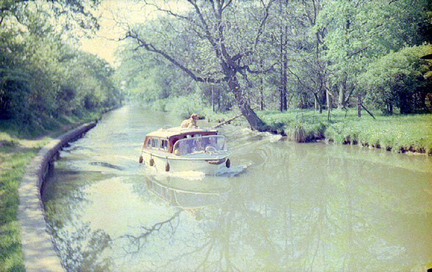 Small cabin cruiser, with Mrs Colledge on board, on the Oxford canal at Cathiron, Brinklow.  May 17th 1964 |  IMAGE LOCATION: (Warwickshire County Record Office) PEOPLE IN PHOTO: Colledge, Mrs