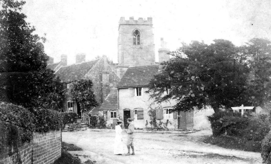 Two people talking in Arley Village with Arley church in the background.  1900s |  IMAGE LOCATION: (Warwickshire County Record Office)