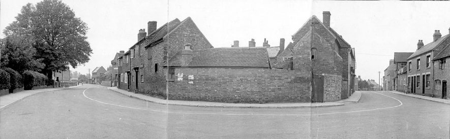 An unusual panorama photograph of the junction of New Street and Rugby Road.  1900s [It has been pointed out that this photograph is actually the junction of School Road, left and Leicester Street. The hedge on the extreme left of the picture was a holly hedge and behind it was the School House. Further up the road on the right can be seen the gable end of a two storey building which was the Old Co-Op which backed on to the Sand Pits. In Leicester Street the building immediately on the left was an off license. In the middle distance on the right hand side of the road can be seen the side view of the gable end of the Rule and Compass public house] |  IMAGE LOCATION: (Warwickshire County Record Office)