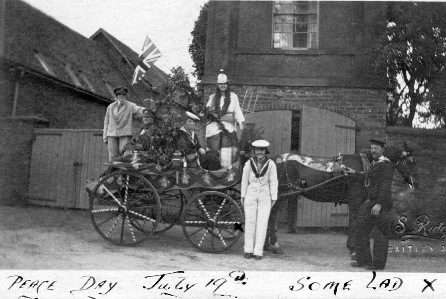 Decorated horse and cart with five men and women in fancy costume at the
