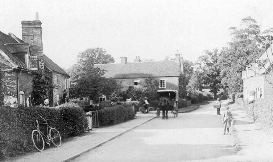 Village street in Ashow, with man delivering goods from horse drawn cart, ladies pushing bikes along street, child carrying bucket and labourer sweeping lane.  1900s |  IMAGE LOCATION: (Warwickshire County Record Office)