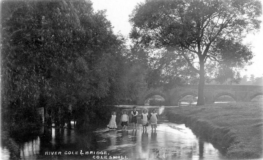 River Cole and bridge, Coleshill, with five children standing in the water.  1910s |  IMAGE LOCATION: (Warwickshire County Record Office)