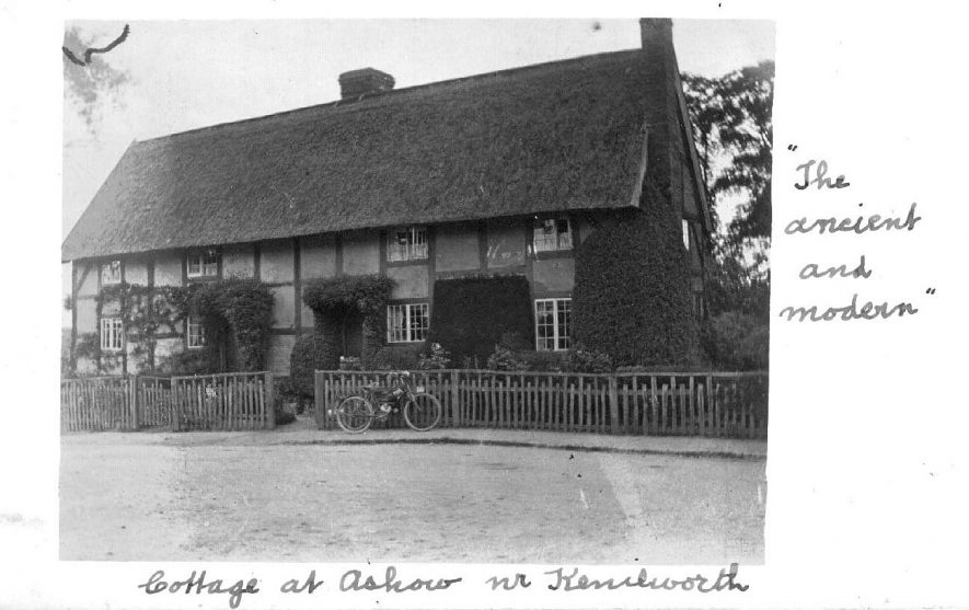 Thatched cottage in Ashow with cottage garden,  wooden fence running along street front and a motorbike, reg. number AC2000, leaning against fence.  1910s |  IMAGE LOCATION: (Warwickshire County Record Office)
