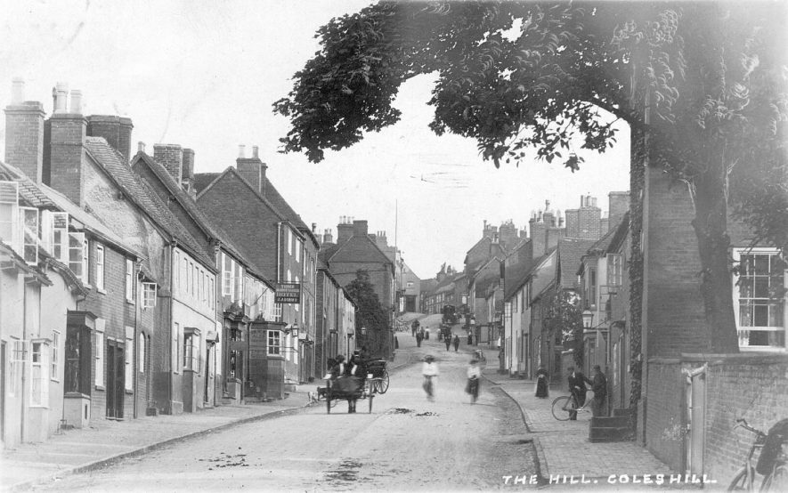 View of houses in The Hill, Coleshill. Horse and cart and people with their bicycles also shown.  1900s |  IMAGE LOCATION: (Warwickshire County Record Office)