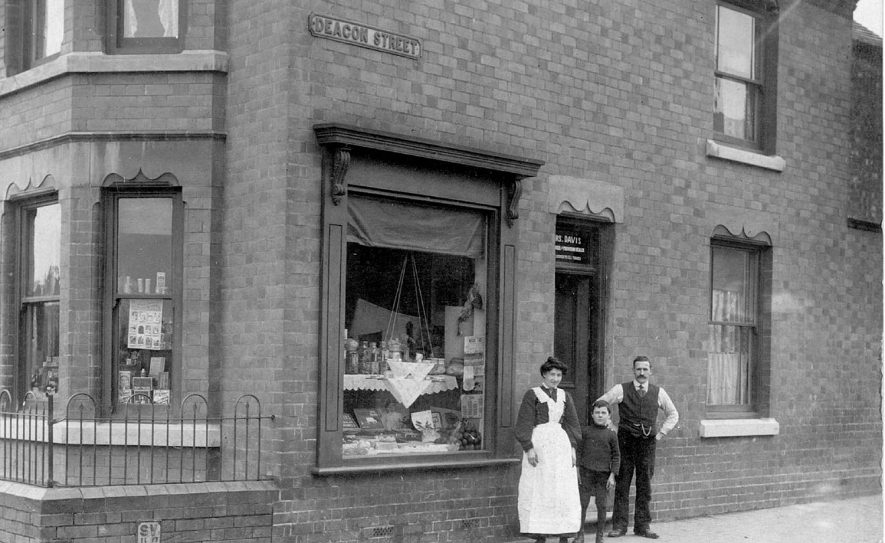 General store on corner of Edward Street and Deacon Street, Chilvers Coton.  Shopkeeper Miss Alice Daws.  Man, woman and boy by doorway.  1910s |  IMAGE LOCATION: (Warwickshire County Record Office) PEOPLE IN PHOTO: Daws, Miss Alice