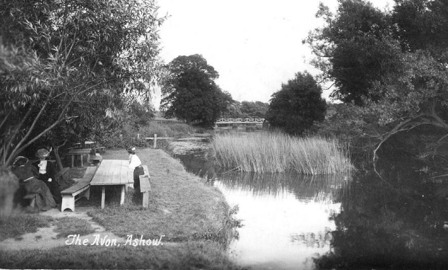 Three ladies sitting at picnic benches, reading,  beside the river Avon, at Ashow.  1907 |  IMAGE LOCATION: (Warwickshire County Record Office)
