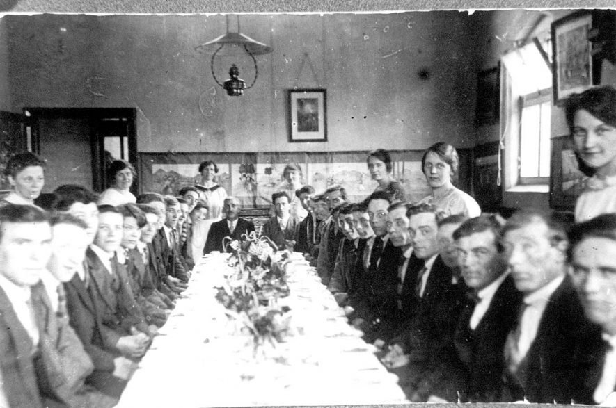 Arley Rectory football club dinner in the old C/E school (now a private house). Ladies serving from left to right - Annie Ault, Mrs Ballard, Mrs George Moore, Mrs Edna Chetwynd, Cissie Chetwynd. Seated at the end of the table on the left - Mr George Moore and on the right Chimpy Moore. Harry Chetwynd is two from G Moore on the left hand side of table. The school caught fire in 1910, this must be in the rebuilt building.  1930s |  IMAGE LOCATION: (Warwickshire Museums. Photographic Collections.) PEOPLE IN PHOTO: Moore, Mrs George, Moore, George, Moore, Chimpy, Chetwynd, Harry, Chetwynd, Edna, Chetwynd, Cissie, Ballard, Mrs, Ault, Annie