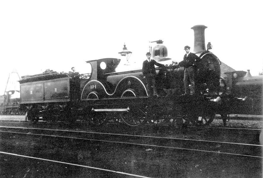 Midland Railway 2-4-0 No.104 engine with R. John Thomas Stain and his brother William at the turn of the century. The locomotive is in full Midland livery and in 1907 became No. 200.  1900s |  IMAGE LOCATION: (Warwickshire Museums. Photographic Collections.) PEOPLE IN PHOTO: Stain, William, Stain, John Thomas