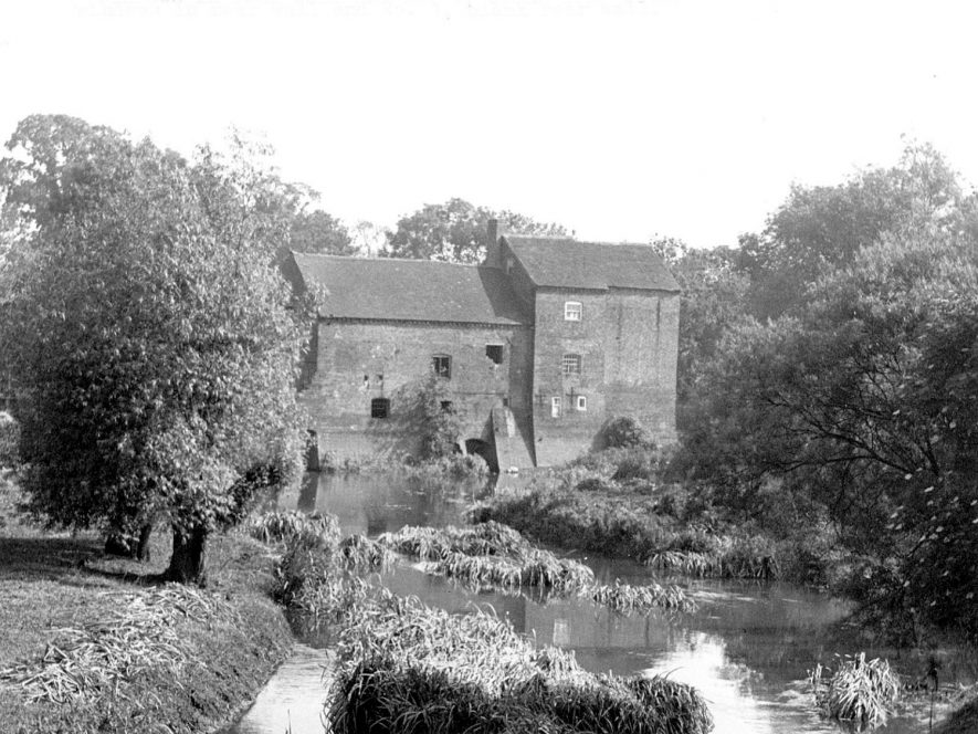 The front of Alders Mill at Atherstone taken from Fieldon Bridge where the pool water flows into the River Anke.  The disused mill is on the left;  cottage no.2, had windows in the rear wall, and No. 1 had a blank rear wall.  1950s |  IMAGE LOCATION: (Warwickshire Museums. Photographic Collections.)