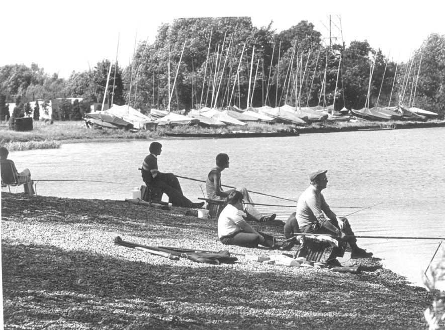 Group of fishermen with sailing boats on the far bank of a lake at Kingsbury Water Park.  1970s |  IMAGE LOCATION: (Warwickshire Museums. Photographic Collections.)