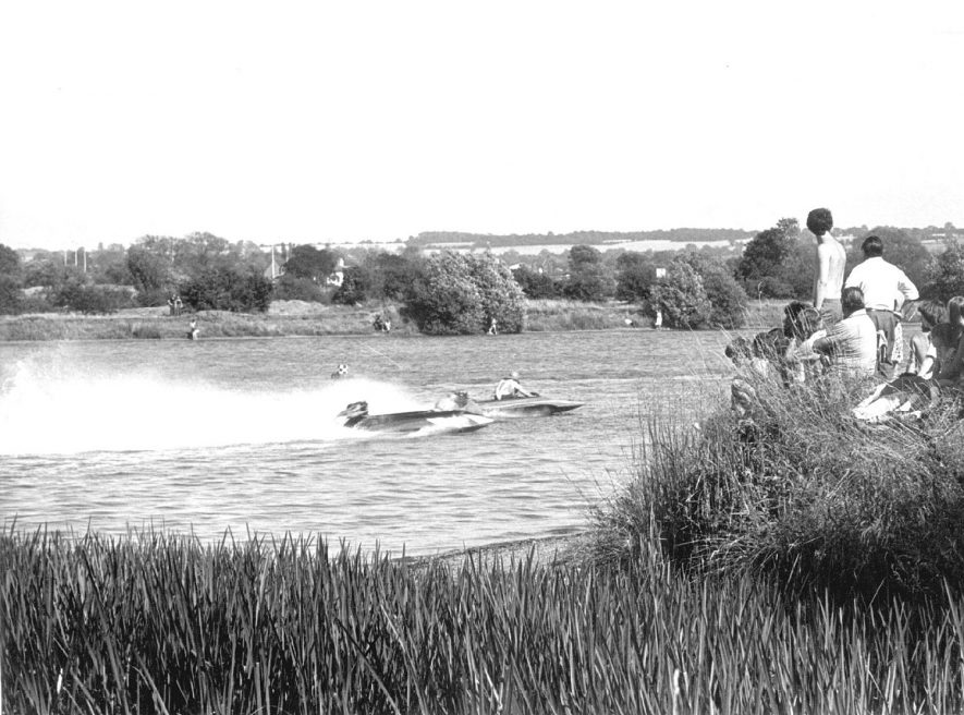 Speedboats on a lake at Kingsbury Water Park with onlookers on the bank.  1970s |  IMAGE LOCATION: (Warwickshire Museums. Photographic Collections.)