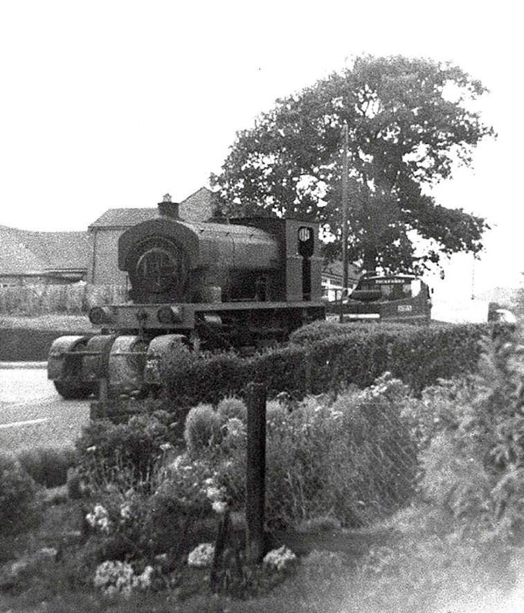 Colliery locomotive being transported on a low loader, and  photographed outside no 63 Gun Hill, Arley.  1950s |  IMAGE LOCATION: (Warwickshire Museums. Photographic Collections.)
