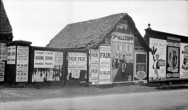 Bill posters on buildings and hoardings in Atherstone.  1950s |  IMAGE LOCATION: (Warwickshire Museums. Photographic Collections.)