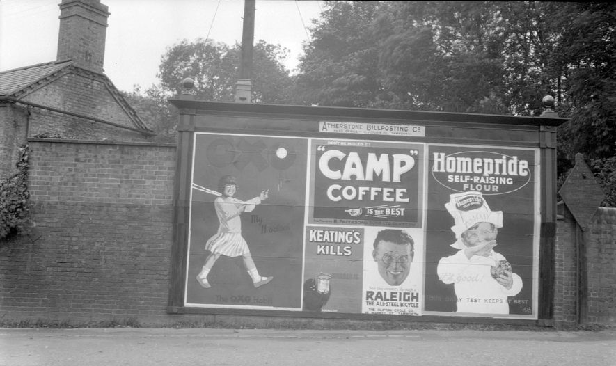 Billposters on an advertising hoarding in Grendon Terrace, Atherstone. The metal plate next to the