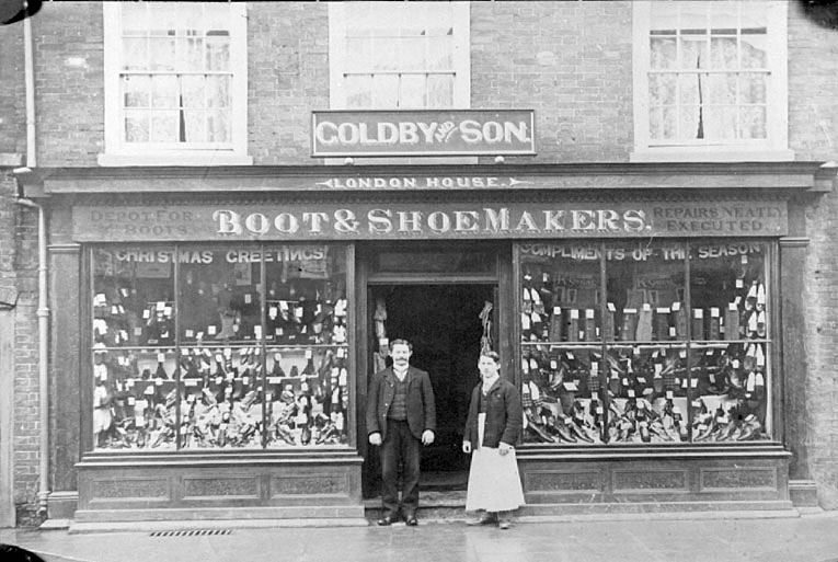 Goldby & Son Boot & Shoemaker shop front with man and woman at door, Coleshill.  1900s |  IMAGE LOCATION: (Warwickshire Museums. Photographic Collections.)
