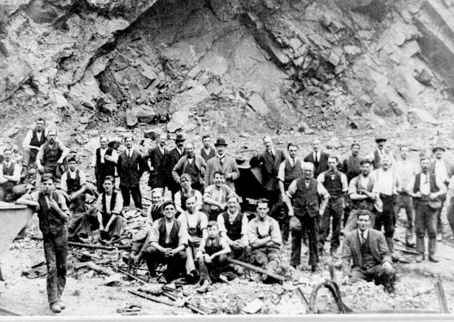 Midland Quarry and group of quarrymen, Nuneaton. The following identified by Mr Harry. D. Ensor, owner of quarry: back 5th from L. Harold Ensor (in jacket & tie) Harry's father, 10th from L. (in bowler) John Ensor (grandfather) 11th from L. Jack Ensor (father's elder brother) 13th from L. Bert Ensor (uncle) 6th from L. George Ensor (uncle). David Ensor (great-grandfather) purchased quarry from Midlands Quarry Co. who started operations in 1876. 1920s |  IMAGE LOCATION: (Warwickshire Museums. Photographic Collections.) PEOPLE IN PHOTO: Ensor, John, Ensor, Jack, Ensor, Harry E, Ensor, Harold, Ensor, George, Ensor, Bert, Ensor as a surname