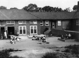 Group of children playing outside Hartshill Infants school.  1941 |  IMAGE LOCATION: (Warwickshire County Record Office)