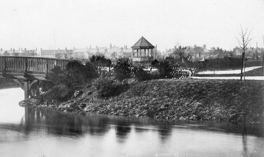 Riversley Park, Nuneaton with River Anker and wooden bridge in the foreground and bandstand behind.  1900s |  IMAGE LOCATION: (Warwickshire County Record Office)
