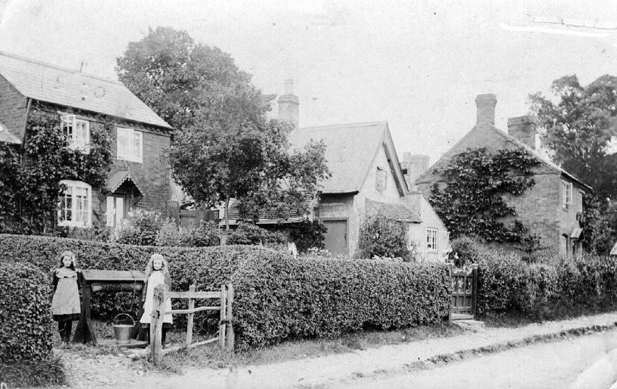 Ashorne village street showing two girls filling a water pail from the well.  1912 |  IMAGE LOCATION: (Warwickshire County Record Office)