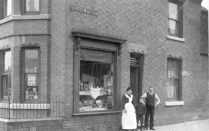 Mrs Alice Davis, shopkeeper, standing outside her shop on the corner of Deacon Street and Edward Street, Chilvers Coton. Pictured with her are a man and a boy.  1910s |  IMAGE LOCATION: (Warwickshire County Record Office)